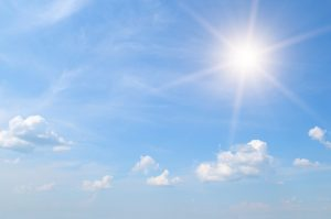 sun on blue sky with white clouds