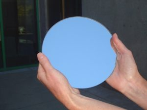 Hands holding a circular mirror reflecting the blue sky.